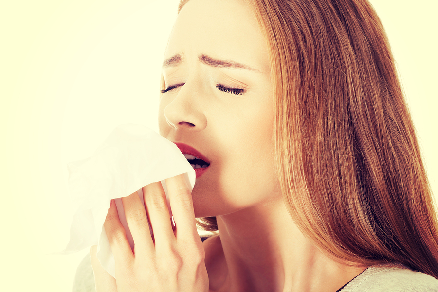 Beautiful caucasian woman sneezing, holding a tissue.